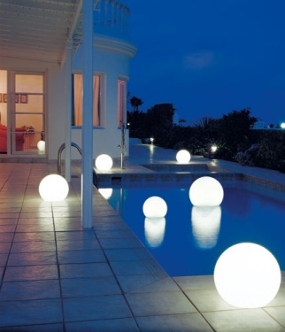 Una pileta exterior iluminada con bulbos